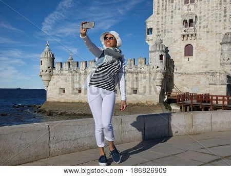 Young woman taking a selfie photo at the Belem tower in Lisbon Portugal
