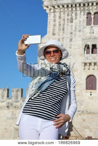 Woman taking a selfie photo at the Belem tower in Lisbon Portugal