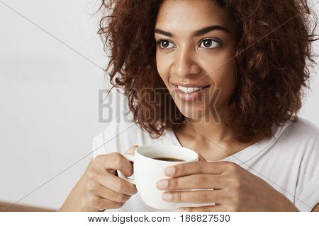 Close up portrait of beautiful african girl smiling holding cup of coffee. Copy space.