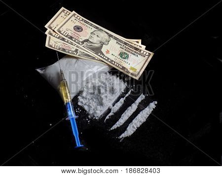 Injection syringe on cocaine drug powder bag, pile and lines and dollar money bills on black background, drug addiction