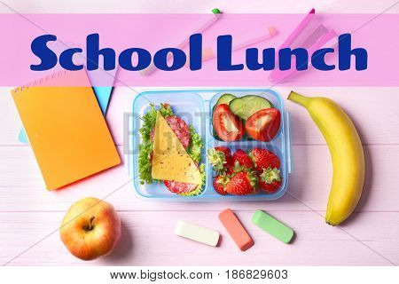 Concept of school lunch. Lunchbox, food and stationery on wooden background