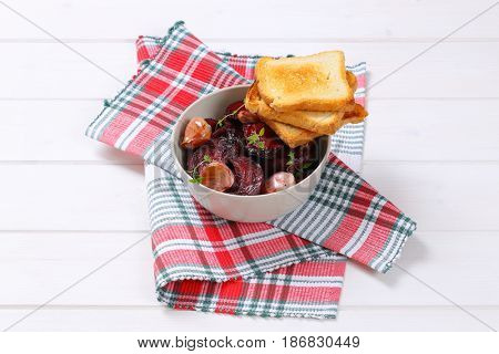 bowl of baked beetroot with garlic and toasts on checkered dishtowel