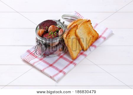jar of baked beetroot with garlic and toasts on checkered dishtowel