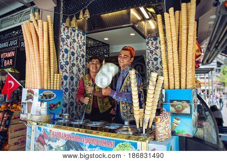 ISTANBUL TURKEY - APRIL 28 2017: Young cheerful dondurma ice-cream sellers dressed in traditional Turkish costume in the street shop
