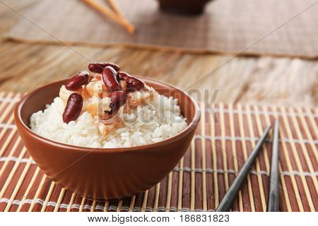 Bowl with tasty chicken, rice and beans on wicker mat