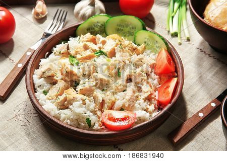 Delicious rice with chicken and vegetables in bowl on table