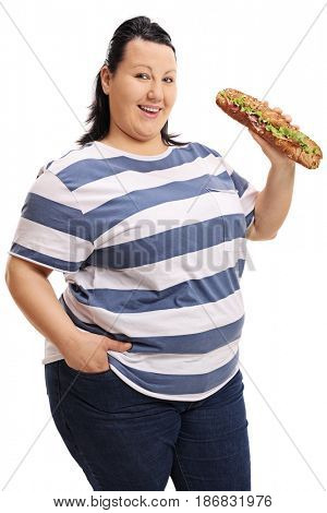 Overweight woman with a sandwich looking at the camera and smiling isolated on white background