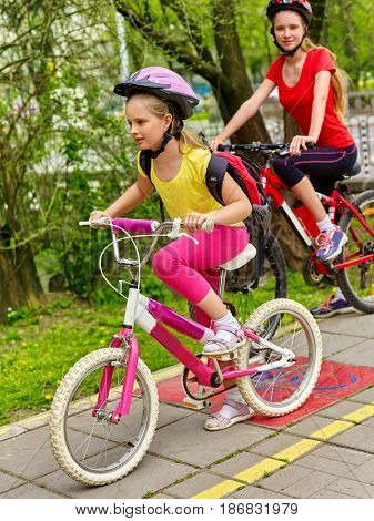 Bicycle path and sign with children. Girls wearing helmet with rucksack ciclyng ride. Kids are on yellow bike lane. Alternative to urban transport. Sisters compete in speed for cycling.