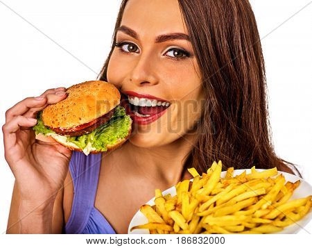 Woman eating french fries and hamburger. Portrait of student consume fast food on table. Girl trying to eat junk. Advertise fast food on daek background. Girl is having supper after hard day's work.