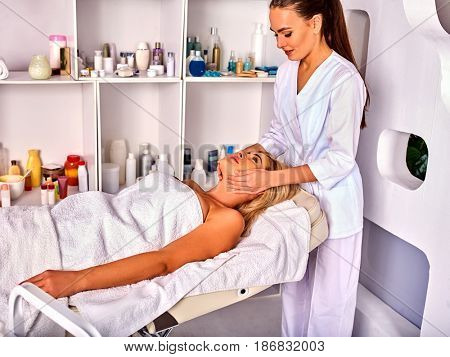 Mature spa and massage deals. Facial anti-aging treatment for forty five year old women . Elderly woman middle-aged take face cleaning in European spa salon. Interior with cosmetic background.