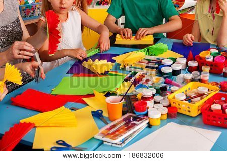 School children with scissors in kids hands cutting paper with teacher in class room. Still life of body part of colored paper and pencils. Children's project in kindergarten.