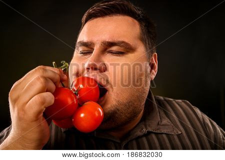 Diet fat man eating healthy food. Health breakfast with vegetables tomatoes for overweight person. Male trying to lose weight and rejoices in healthy eating. Fat man enjoying cherry tomatoes.
