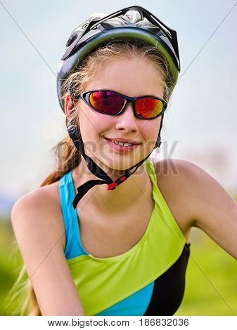 Woman on bicycle ride mountain. Girl traveling in summer park. Early morning with blue sky and clouds. Cycling person with rucksack. Sport trip is good for health. Portrait of beautiful extreme sport