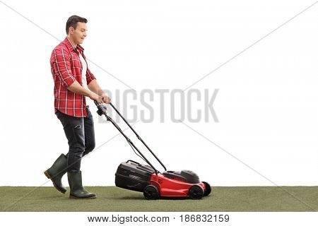 Full length profile shot of a gardener mowing a lawn with a lawnmower isolated on white background