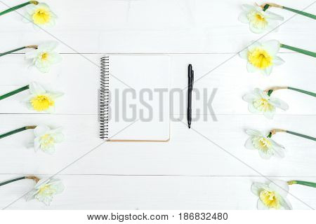 Yellow bouquet of narcissus on white wooden background. Blank card flat lay. Top view on table with narcissus empty diary and pencil copy space