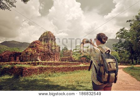 Traveller photographing ancient ruins ensemble of ancient Hindu temples My Son. Vietnam Built by the Kingdom of Champa in Central Vietnam. UNESCO World Heritage Site