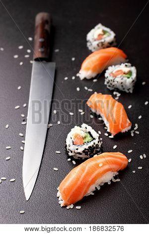 Sushi nigiri sushimi with salmon and roll sushi philadelhia with knife for sushi. Over stone background.Copy space .Sushi menu. Japanese food.
