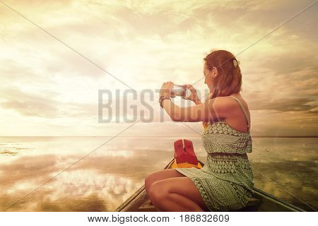 Attractive female tourist in a dress photographing on the smartphone a sunset with a picturesque reflection in water Summer holiday travel and technology outdoors.