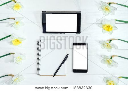 Top view on table with narcissus empty diary pencil tablet and phone free space. Yellow narcissus on white wooden background. Blank card flat lay