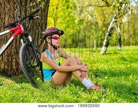 Woman traveling bicycle in summer park. Bicyclist girl watch on smart watch. Girl counts pulse after sport training. Girl hugs herself by knees is dreaming, looking at sky.
