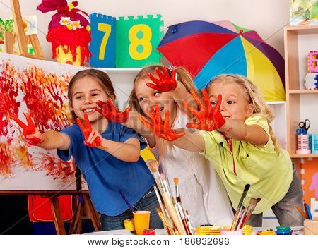 Children painting finger on easel. Small students in art school class. Cheers children in kindergarten. Craft drawing education develops creative abilities of children.