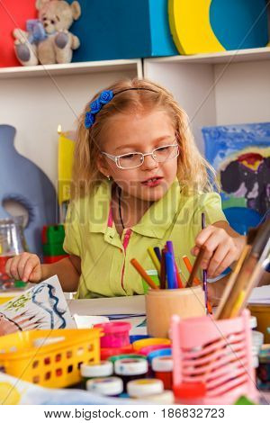 Small student girl painting in art school class. Child drawing by paints on table. Portrait of kids in kindergarten. Craft drawing education develops creative abilities of children. Child chooses