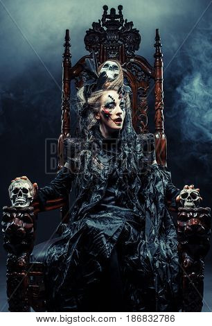 Young beautiful witch sits on a chair. Bright make up, skull, smoke-  halloween theme.