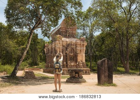 Tourist photographing ancient ruins ensemble of ancient Hindu temples My Son. Vietnam Built by the Kingdom of Champa in Central Vietnam. UNESCO World Heritage Site