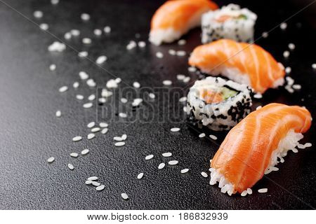 Sushi nigiri sushimi with salmon and roll sushi philadelhia. Over stone background.Copy space .Sushi menu. Japanese food.