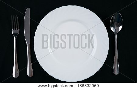 Empty white plate with silver fork knife and spoon isolated on black background. Dinner place setting. Top view