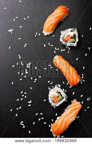 Sushi nigiri sushimi with salmon and roll sushi philadelhia. Over stone background.Copy space .Sushi menu. Japanese food.Top view
