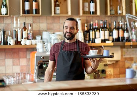 small business, people and service concept - happy man or waiter in apron holding tray with coffee cup and sugar-bowl at bar