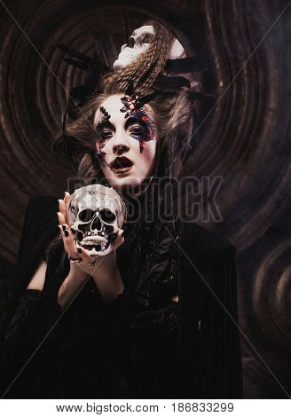 Young  witch hloding skull. Bright make up and  smoke-  halloween theme.