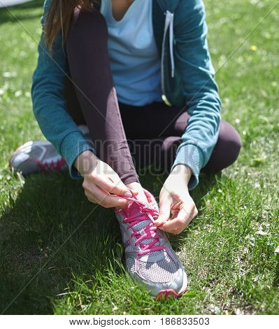 Portrait of young and sporty woman in sportswear doing yoga or Stretching exercises outside at the park on green field on cloudy day, Dnipro, Ukraine. She is sitting on the green meadow between trees and Knots laces on his sneakers before jogging or exerc