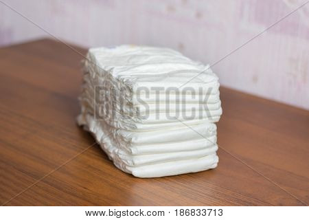 Pack of white diapers on a table. Pampers