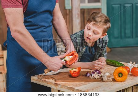 Cute Little Boy Looking At Father Cutting Vegetables On Cutting Board, Dad And Son Cooking Concept