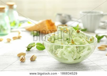 Glass bowl with delicious pistachio ice cream on white wooden table