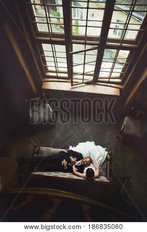 Wedding Couple Rests On The Couch In The Front Of High Window