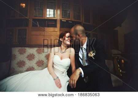 Bride Leands To A Bald-headed Groom Sitting On The Old Couch