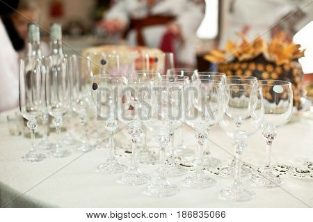 Empty wineglasses stand on the white dinner table