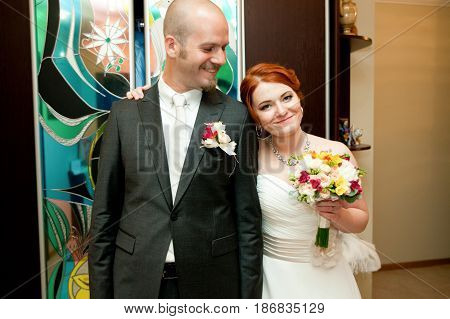 Happy Bride With Red Hair Leans To A Groom Standing In The Room