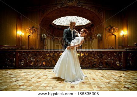 Groom Holds Bride In His Hands Standing In The Middle Of Old Wooden Hall