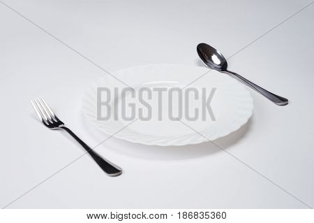 A white plate with silver fork and spoon isolated on white background with copy space. Dinner place setting. Table Setting