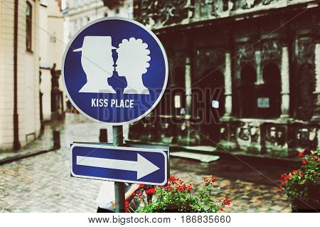 A road marker 'Kiss place' stands on the old city square