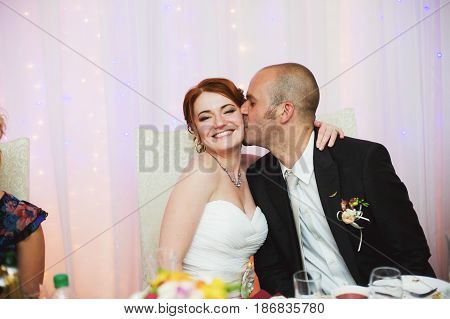 Bald-headed Groom Kisses Bride In A Cheek While Sitting At The Dinner Table