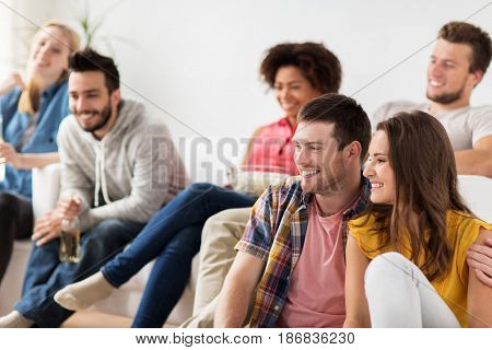 friendship, people and entertainment concept - happy friends with popcorn and beer watching tv at home