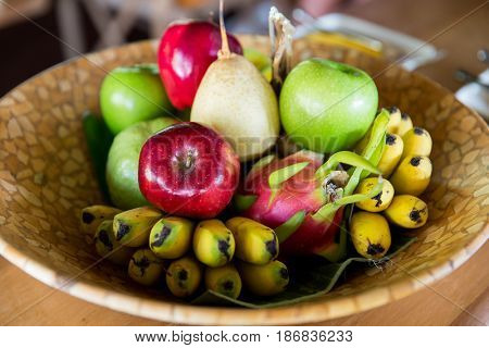 food, eco, bio and summer holidays concept - still life with exotic tropical fruits in bowl