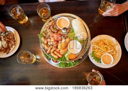 food, drinks and holidays concept - people table with food and beer glasses at bar or pub