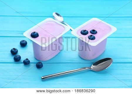 Plastic cups with yogurt and blueberries on wooden table