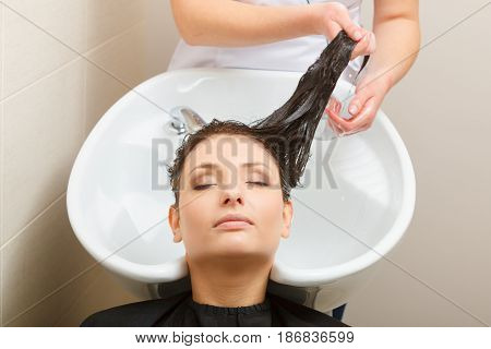 Haircare relaxation and hairstyling concept. Woman sitting in black cape getting her hair washed by hairdresser